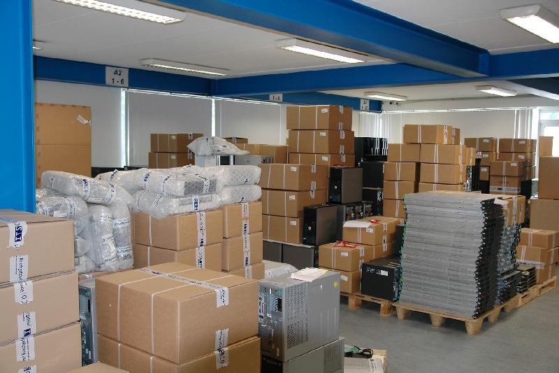 Noch zu verpackende IT-Geräte in der Verpackungsstation und bereits verpackte Geräte, die auf die Weiterführung ins Lager warten.
